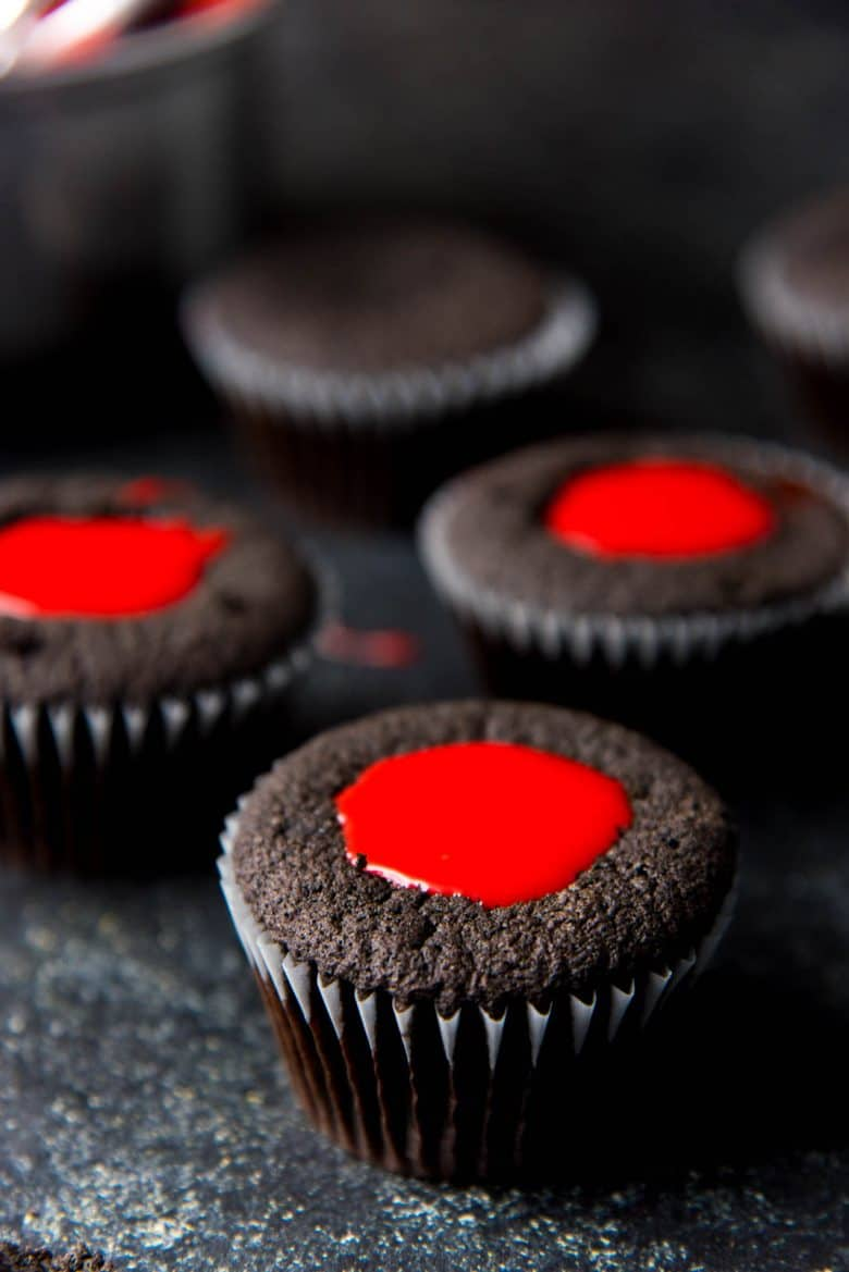 Black cupcakes filled with red chocolate ganache