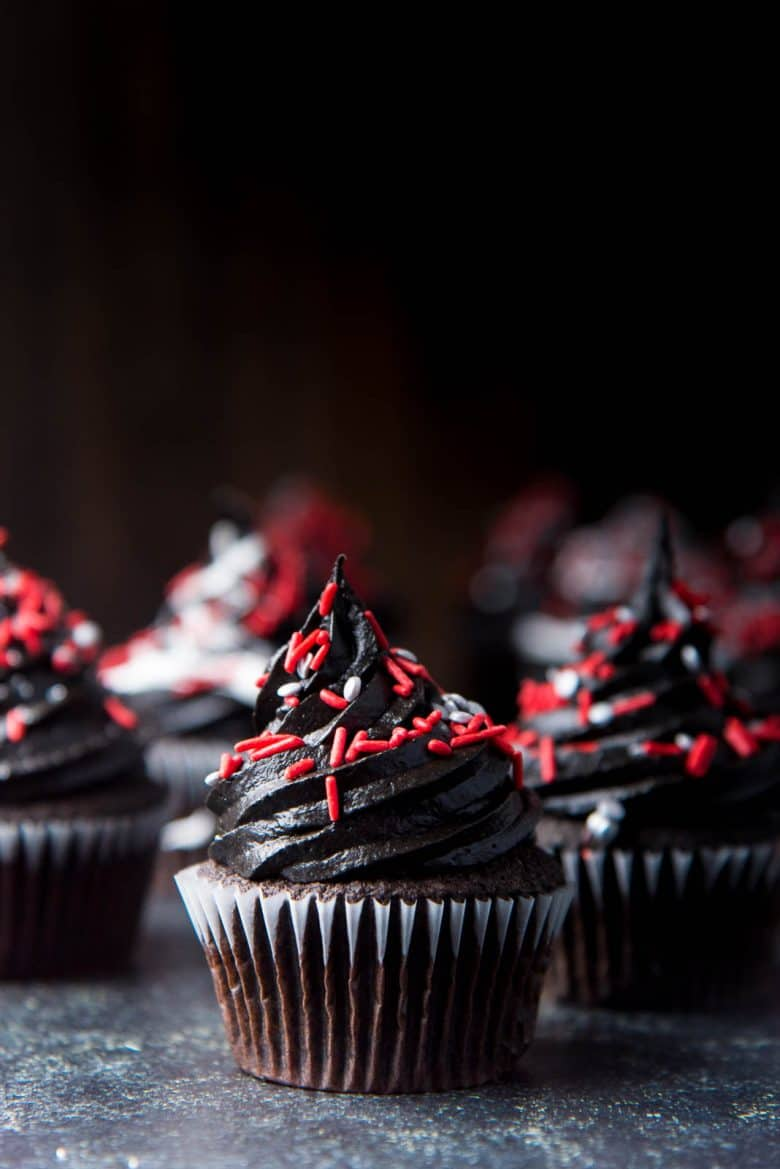 A collection of halloween cupcakes with red and silver sprinkles