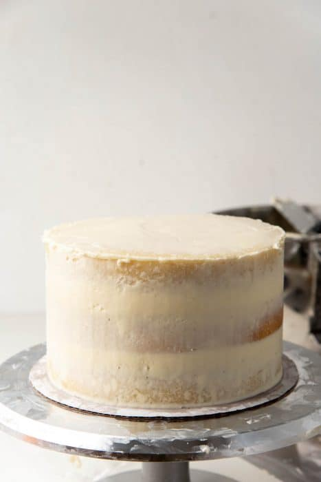 Coconut cake with a crumb coating on a cake turntable