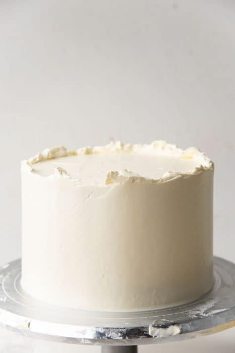 A smooth frosting layer on the coconut cake