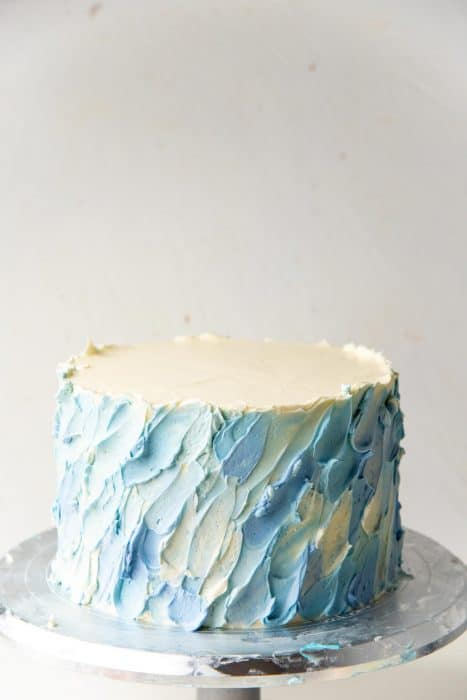 A completed spatula painted coconut cake with a winter cake theme.