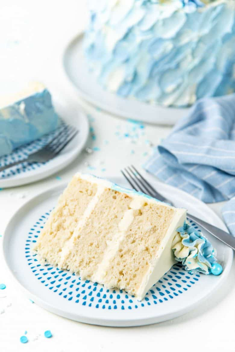 A slice of coconut cake on a blue and white plate
