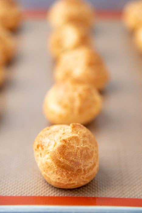 Freshly bakes choux pastry on a baking tray