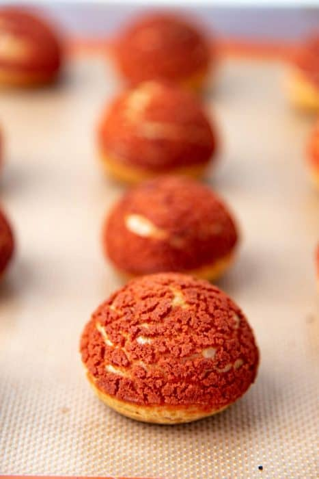 Freshly baked choux pastry with red colored craquelin on top
