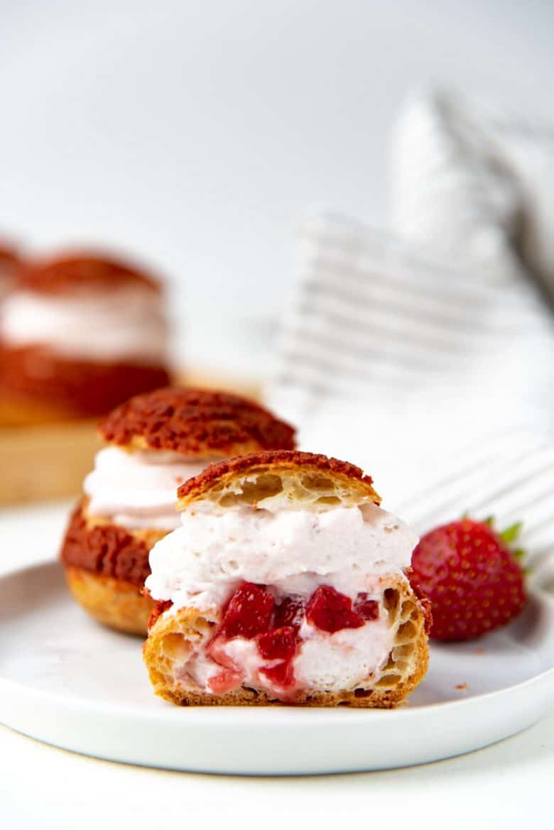 A strawberry cream puff cut in half to show the inside