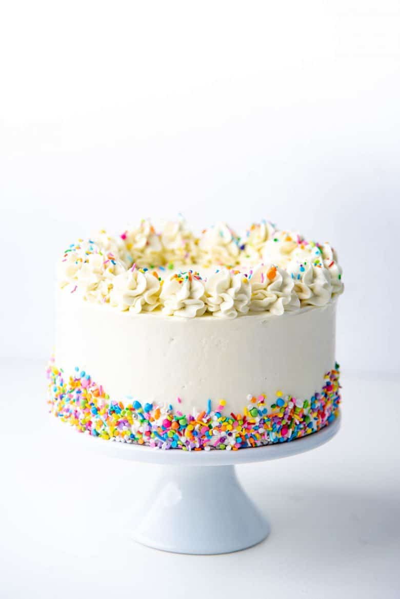 Easy white cake on a cake stand with confetti sprinkles on the side and top