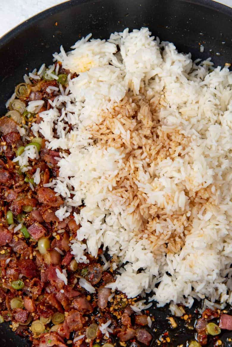 Day old jasmine rice with soy sauce, added to the frying pan, with the bacon mixture