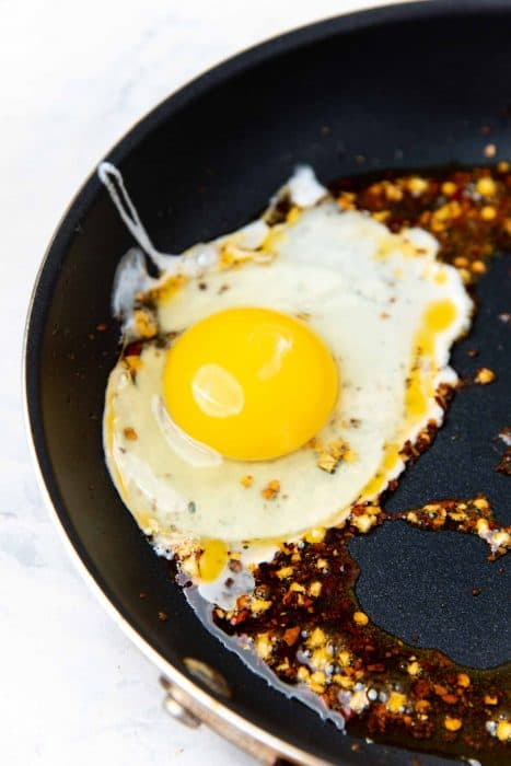 An egg cracked into the frying pan with the hot garlic chili oil, to show how to fry the garlic chili fried egg