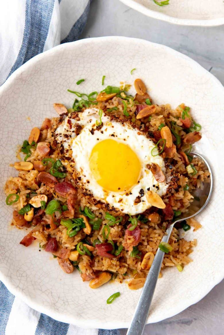 Overhead view of the bacon fried rice, topped with a chili garlic fried egg and roasted peanuts