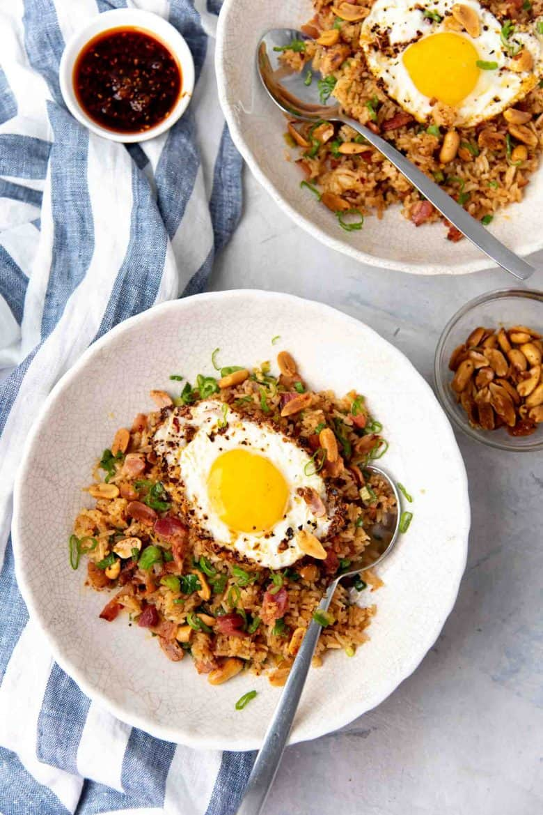 Serving bacon fried rice in two large bowls, topped with runny fried eggs.