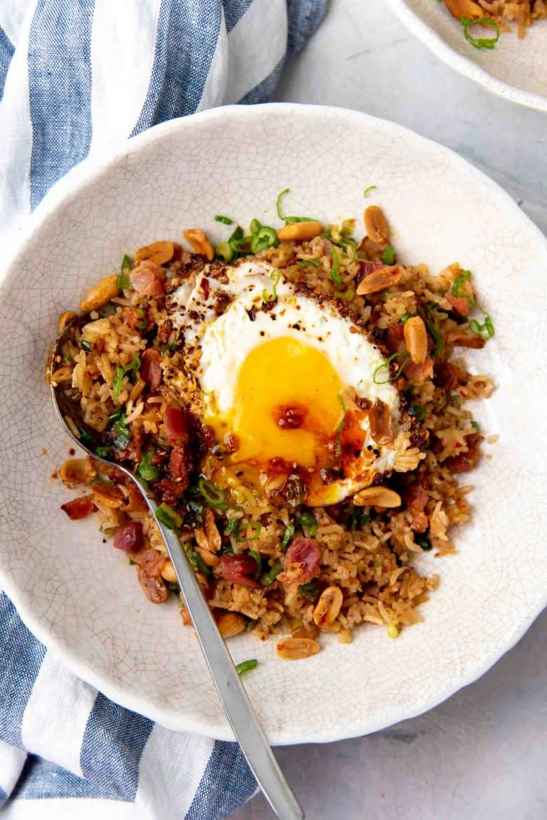 Over head close up view of the bacon fried rice with the yolk and chili oil mixing with the rice.