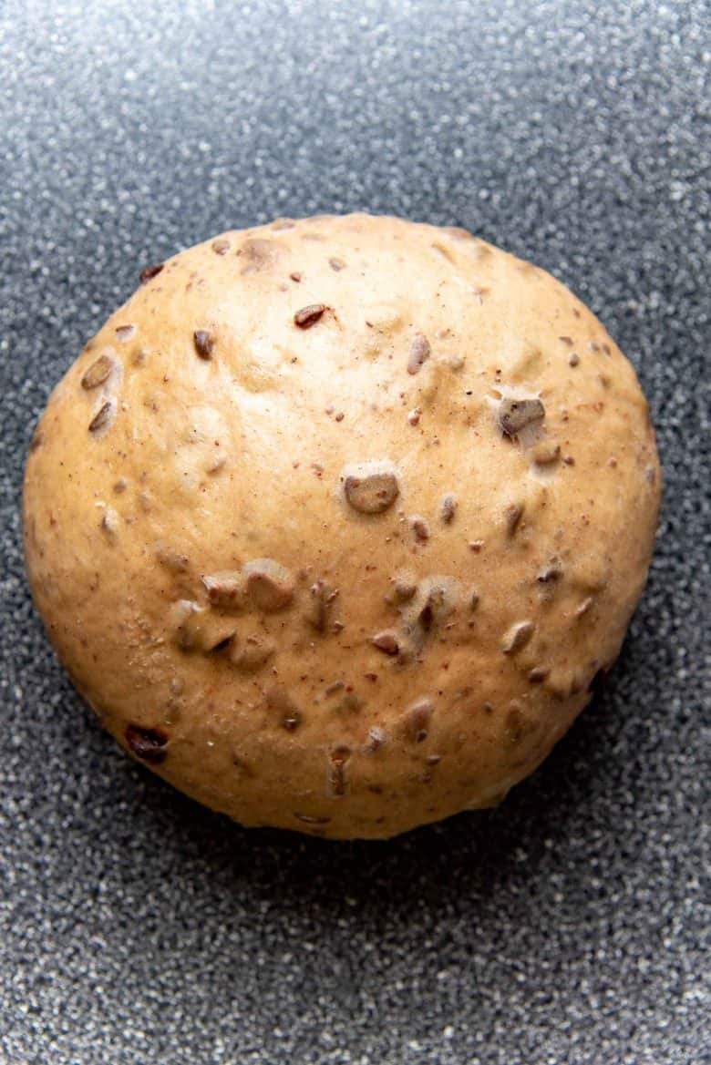 The chocolate chip hot cross buns dough on a work surface