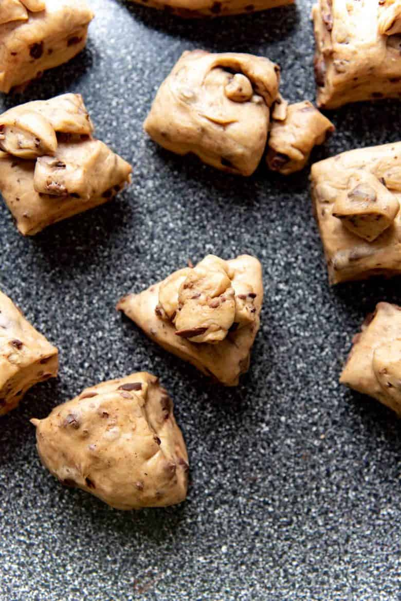 Pieces of the chocolate chip hot cross bun dough, portioned out into irregular pieces on a work surface
