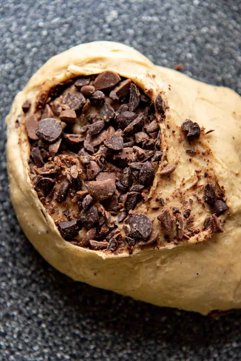 Adding chocolate chips that have been roughly chopped to the hot cross bun dough