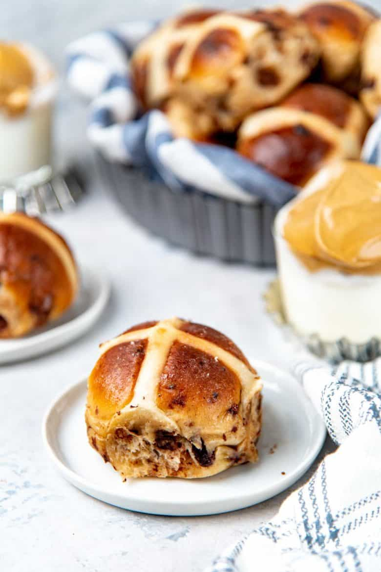 Tablescape of hot cross buns served on small white plates with coffee