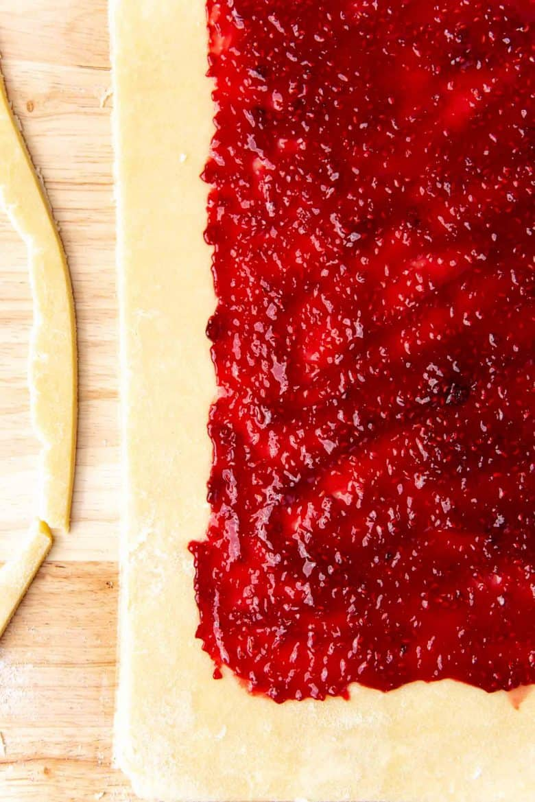 The rolled out pie crust with raspberry jam spread over the surface, leaving a margin around the edge of the crust