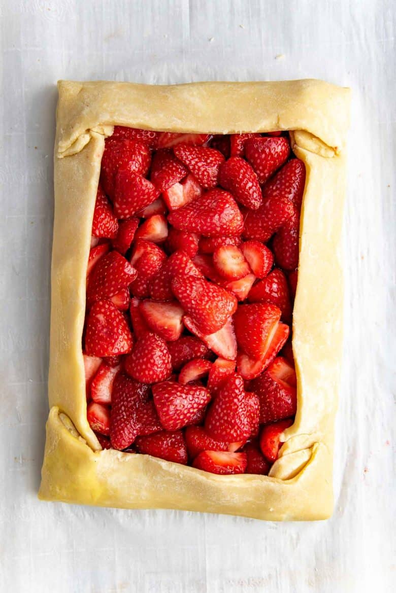 The edges of the pie crust folded over the edges of the strawberry filling, forming a rectangle strawberry galette