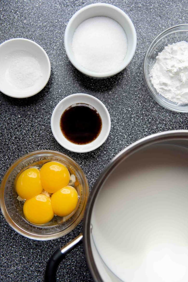 Egg yolks, vanilla, salt, sugar, cornstarch and milk in separate bowls and pans to make homemade vanilla pudding