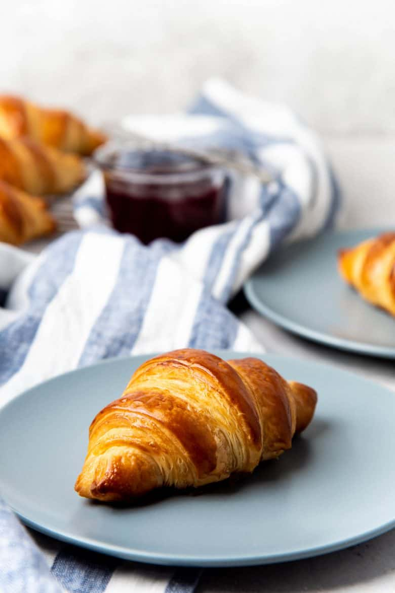 Serving croissants on a plate with jam on the side