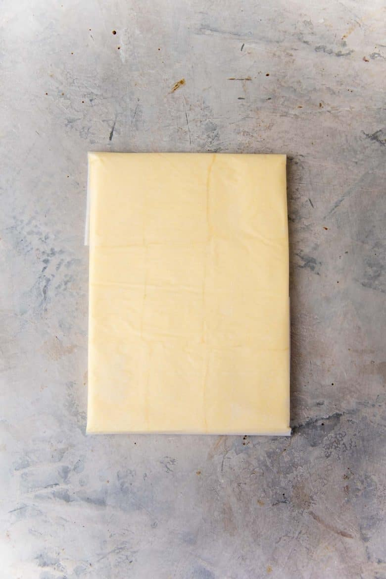The butter has been rolled within the folded parchment paper rectangel