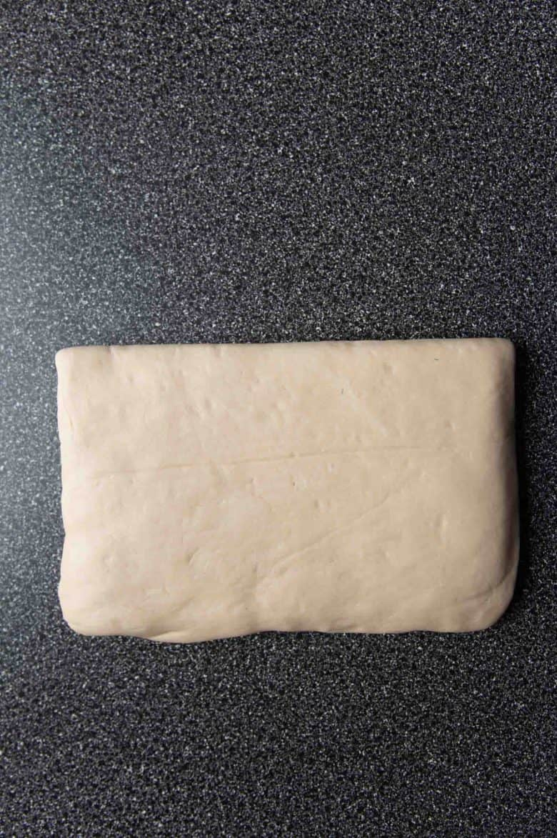 The dough folded over the butter, to enclose the butter before the lamination process.