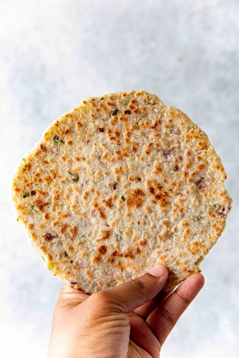 A close up of the pol roti showing the golden brown and brown caramelized spots and red onion and green chili flecks