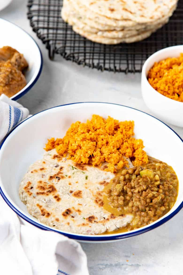 Serving the coconut flatbread with pol sambol and lentil curry in a white plate as a vegan meal