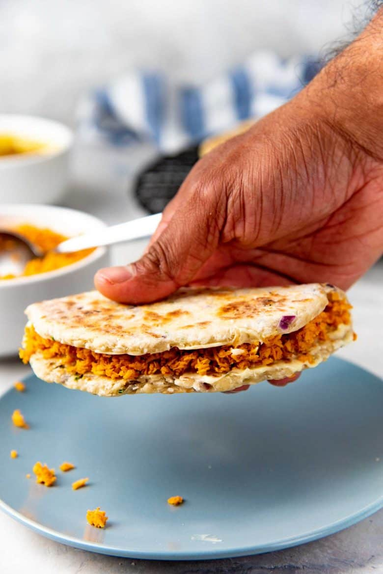 A hand picking up a pol roti sandwich with chili coconut sambal inside