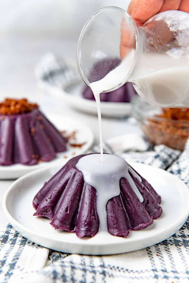 Pouring a sweet salty coconut syrup on top of molded ube halaya