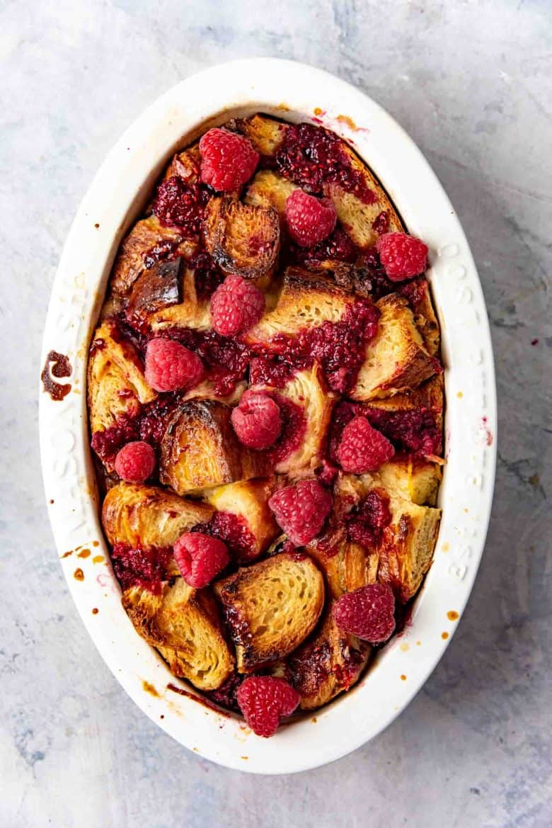 Freshly baked raspberry croissant bread pudding with more fresh raspberries on top.