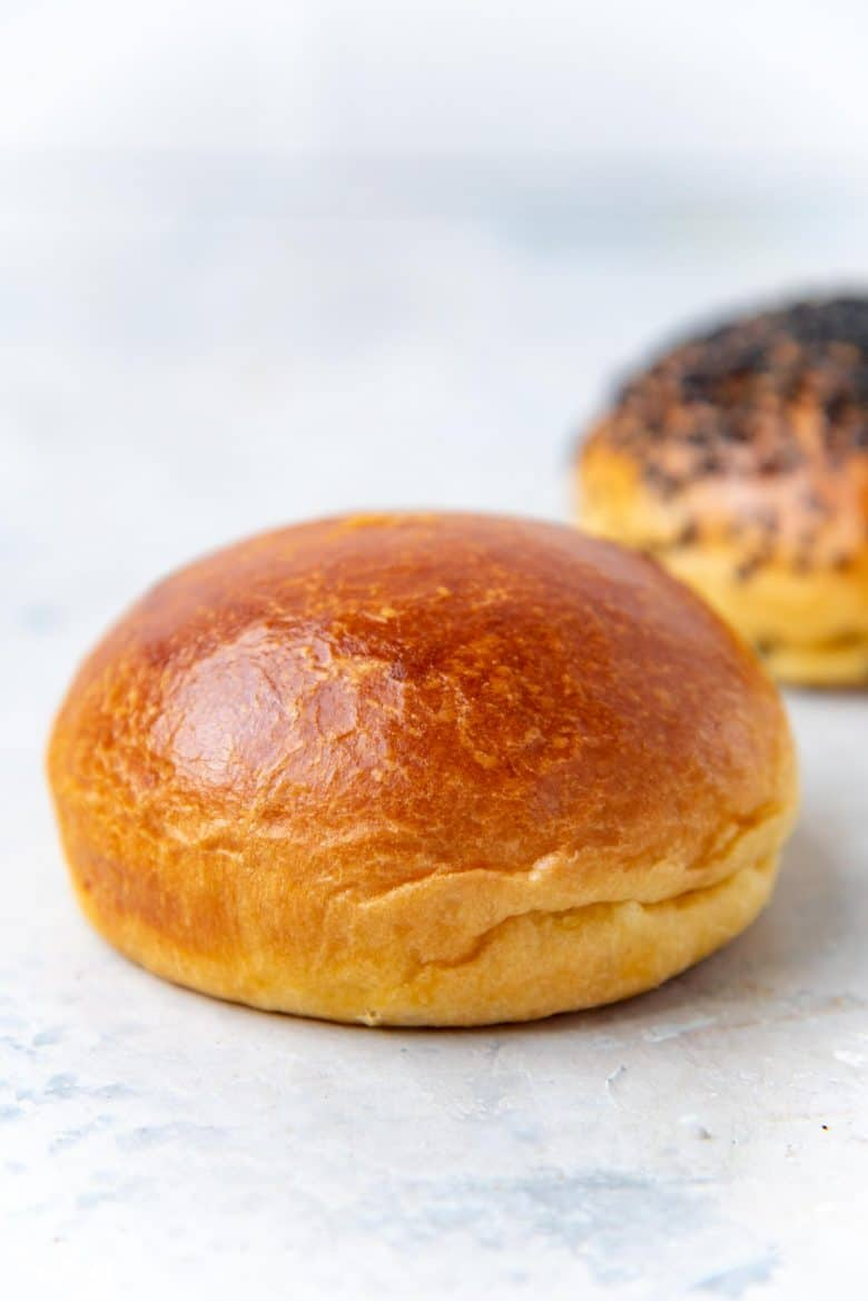 A single brioche bun on a white table top