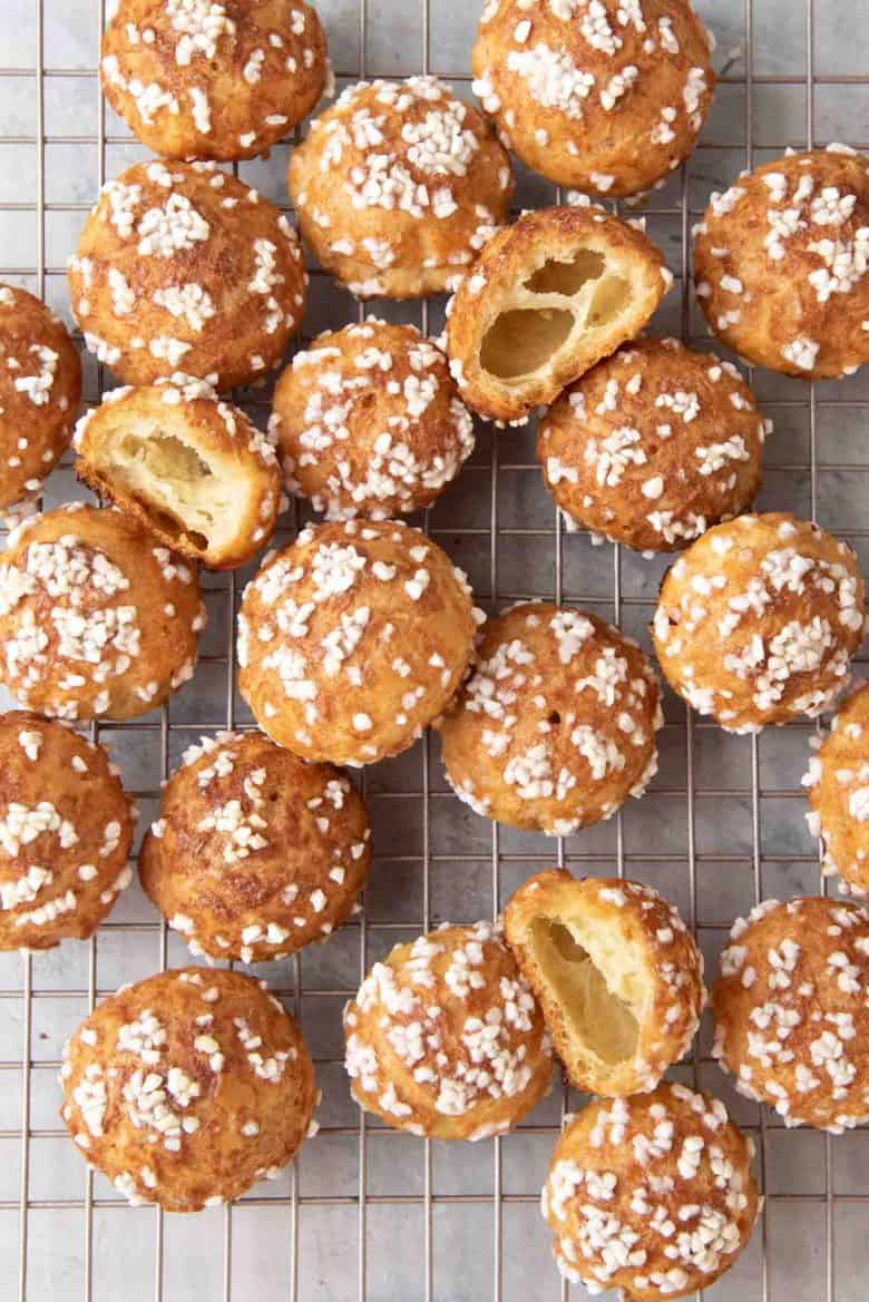 An overhead view of a batch of chouquettes on a wire rack