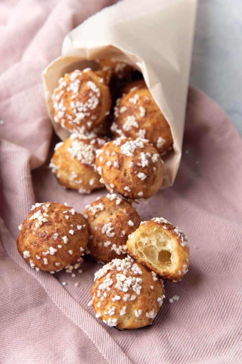 Classic chouquettes, served in a paper cone that is placed flat on a cloth napkin on a table.