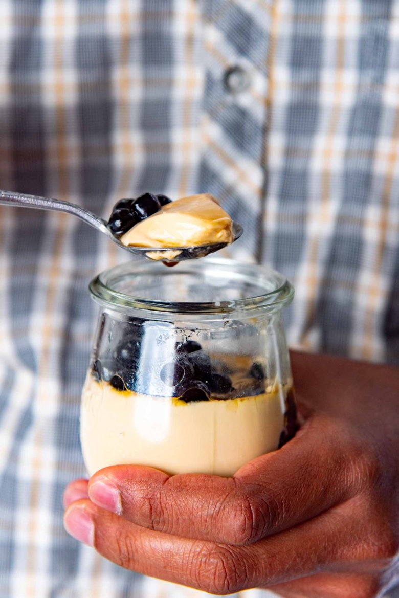A single serving panna cotta held in a hand