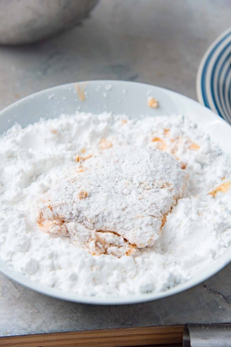 Coating a chicken thigh with potato starch