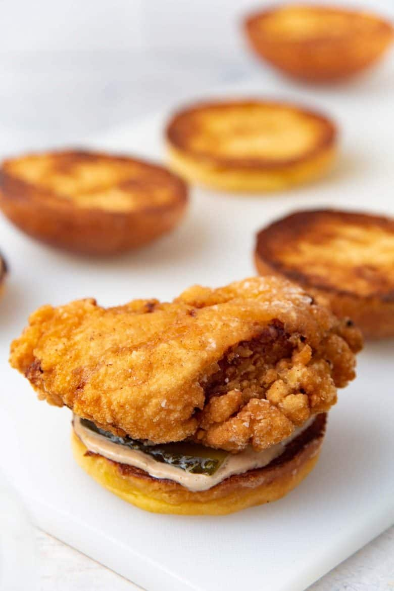 Fried chicken piece placed on top of the pickles on the bun
