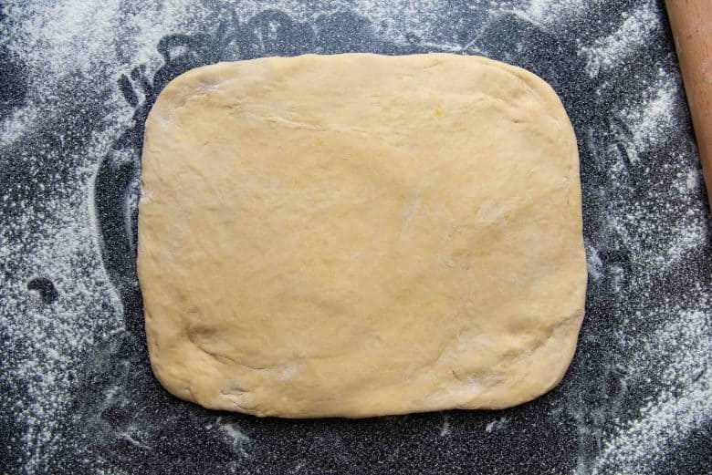 Chilled brioche dough shaped into a rectangle on a floured surface
