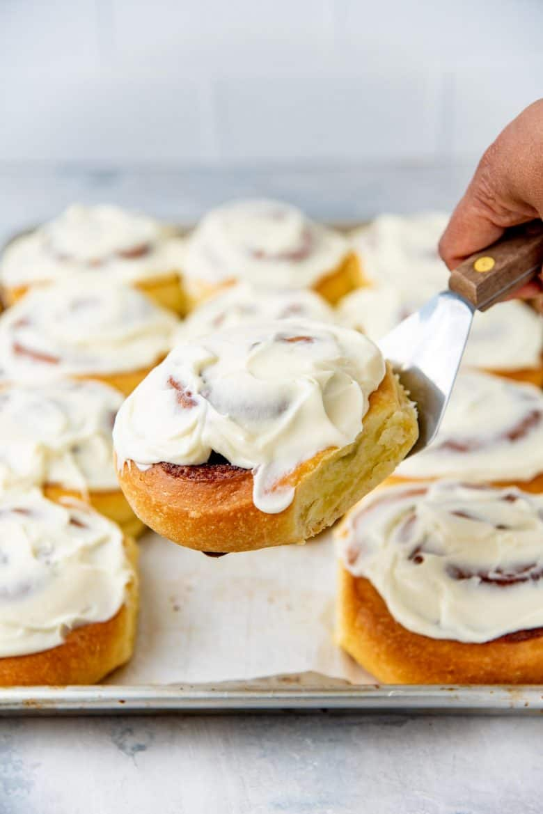 Cinnamon rolls picked up with a spatula with more in the background on a baking tray
