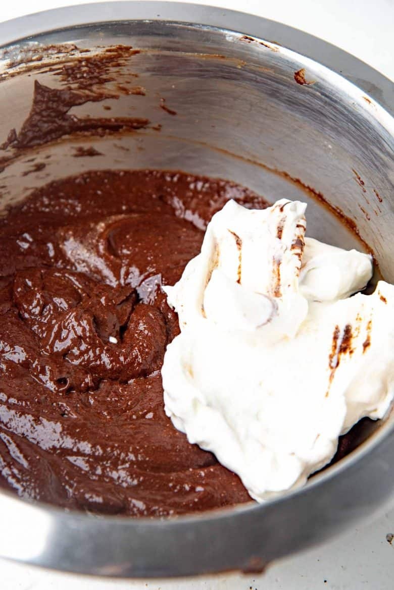 A large dollop of whipped cream on top of the chocolate mousse mixture