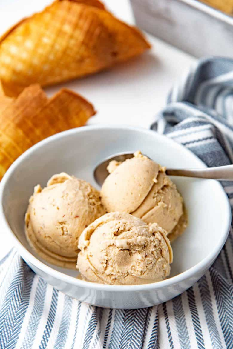 Date and tahini ice cream scoops served in a bowl, with ice cream cones in the background