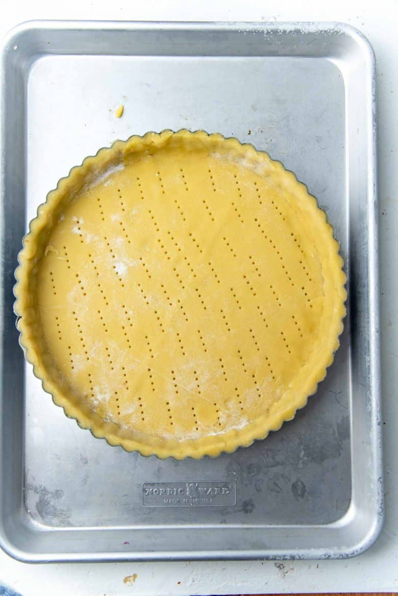 A tart molds lined with pastry dough and docked