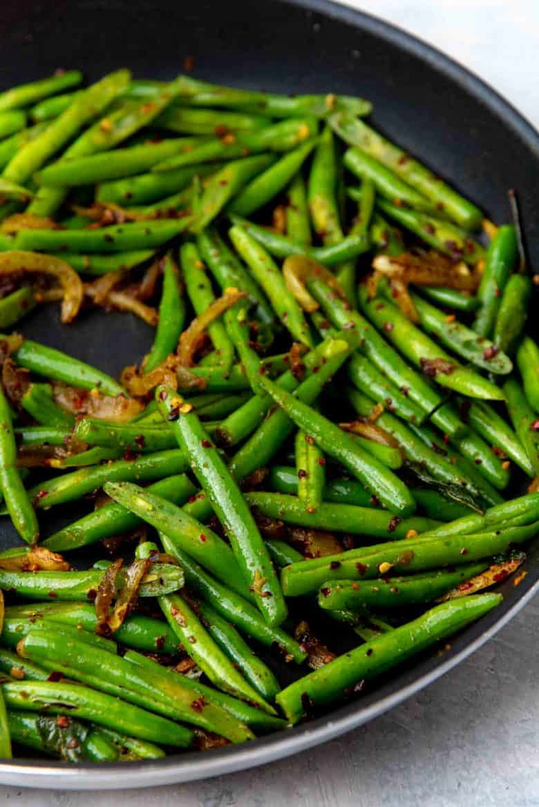 Green beans added to the onions an stir fried