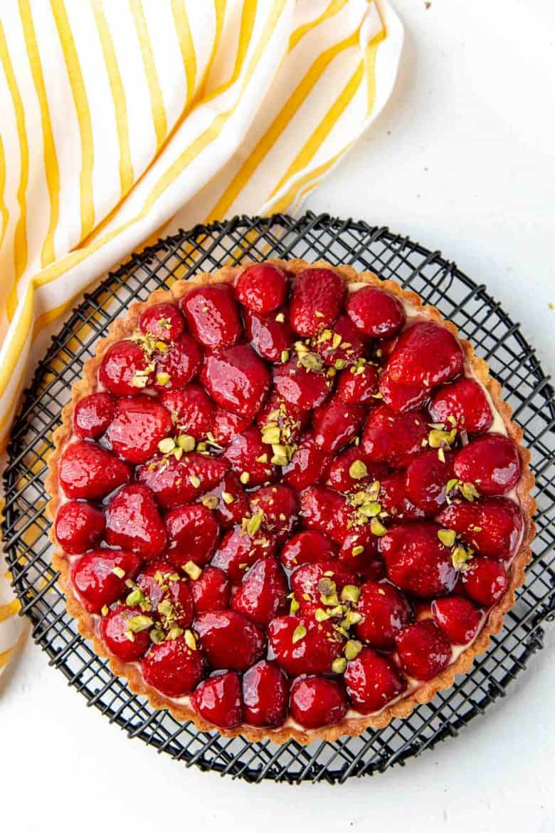 An overhead view of the strawberry tart, decorated with chopped pistachios