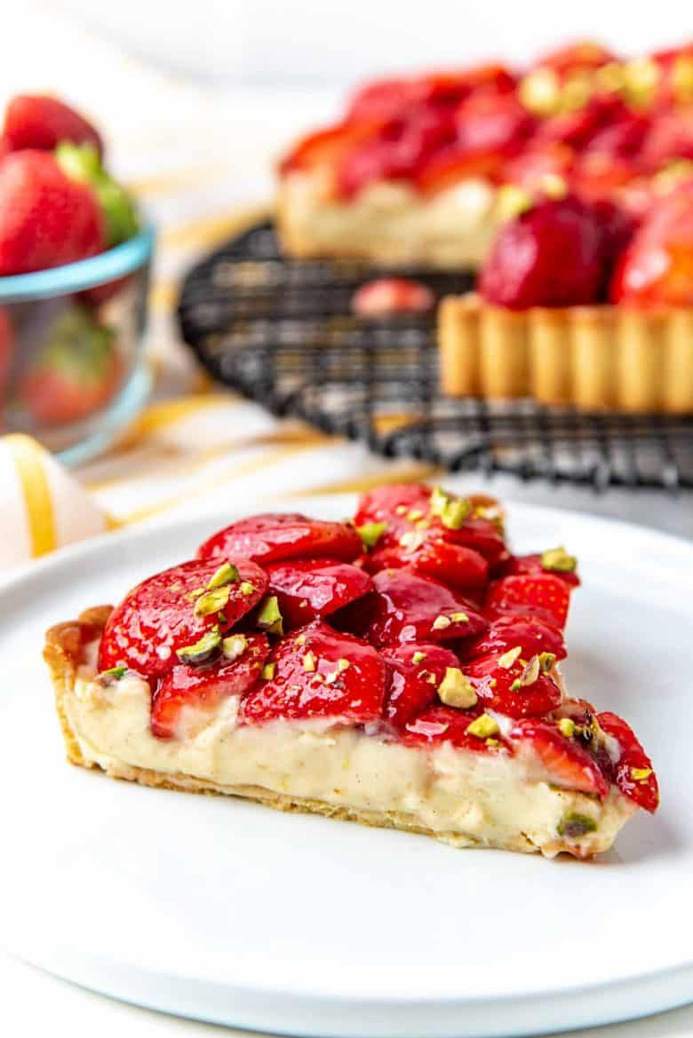 A slice of the strawberry tart served on a white plate