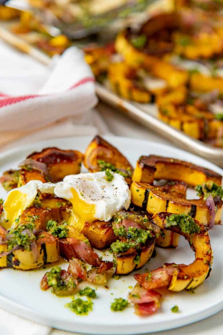 Poached egg broken on top of the bacon roasted delicata squash with pesto
