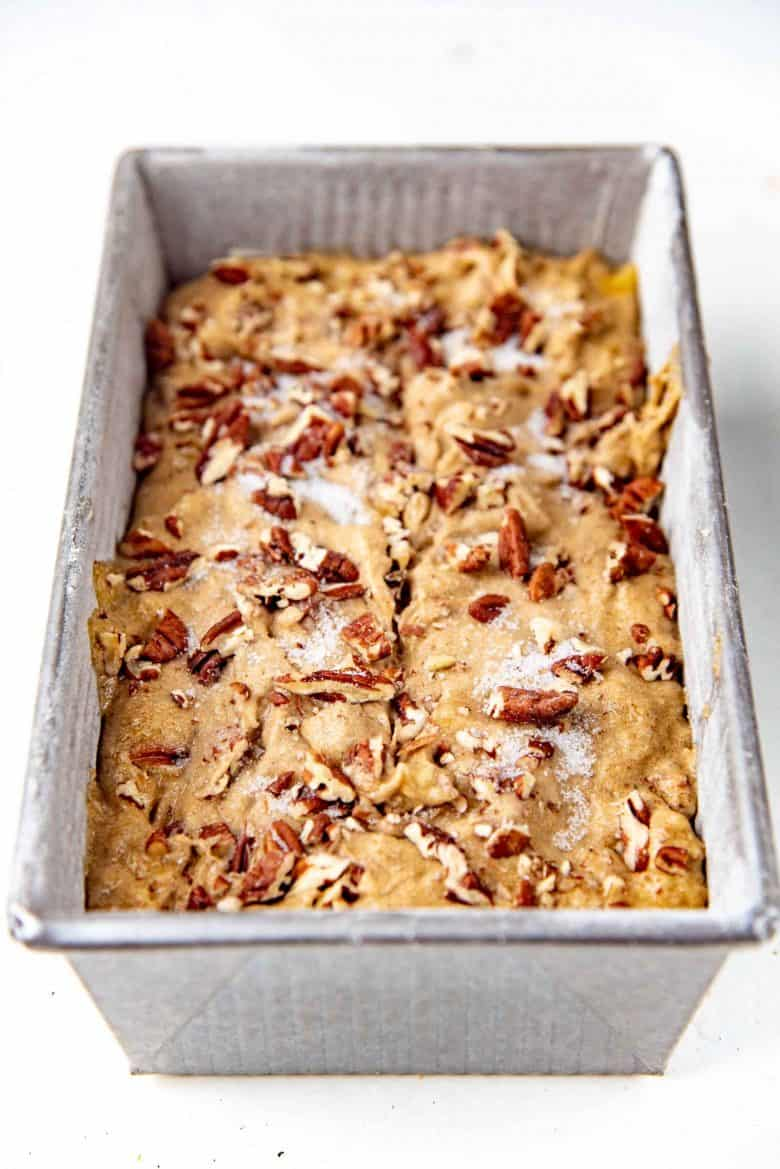 Banana bread in baking pan with nuts on top