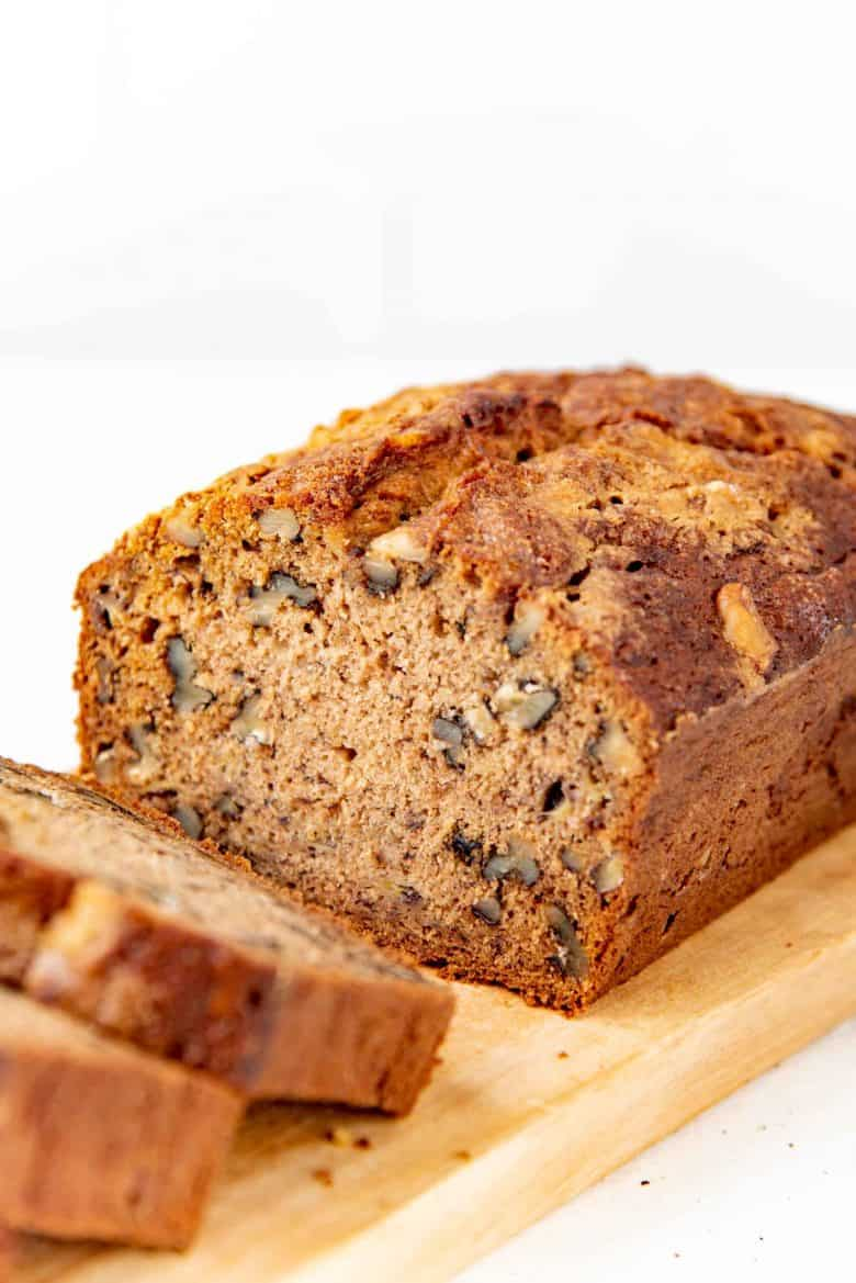 Banana bread sliced on a cutting board, showing the texture and nuts visible