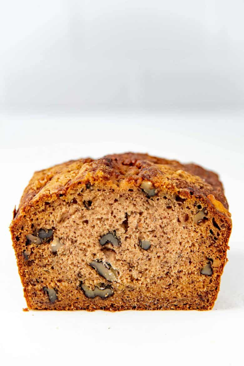 A side on view of the inside of the banana bread loaf, showing the texture and nuts