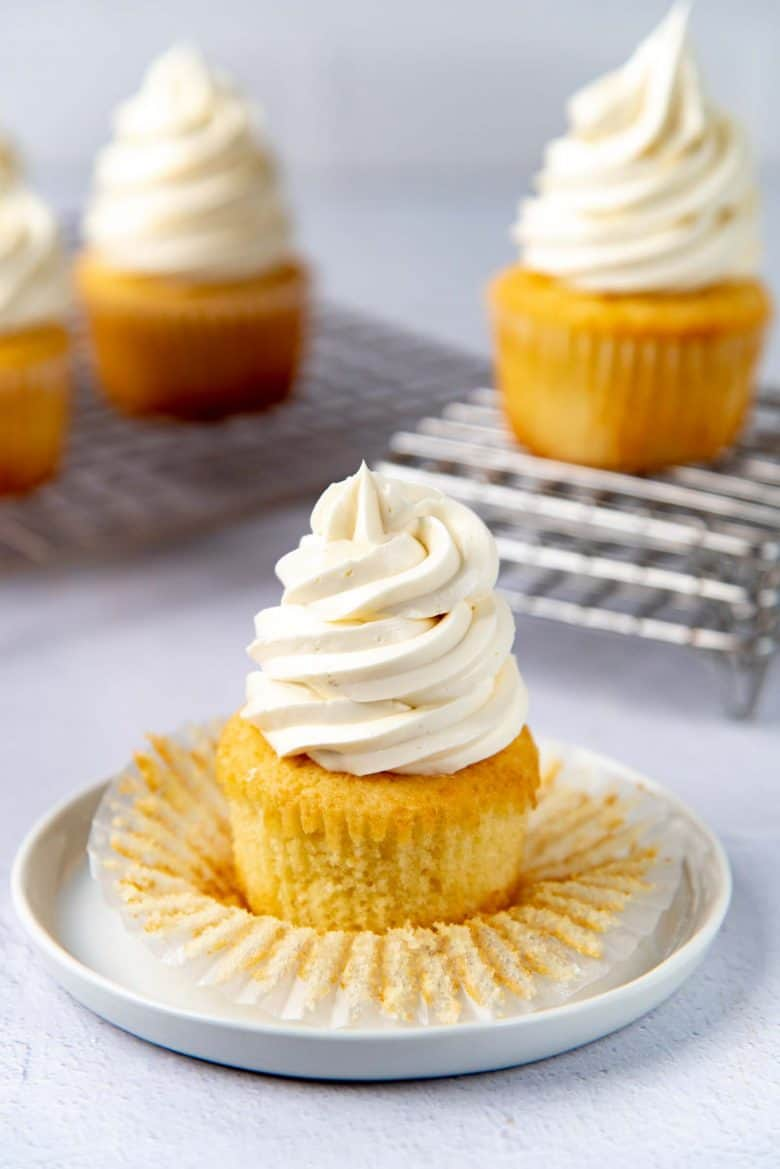 Unwrapped vanilla cupcakes piped with vanilla frosting on a white plate