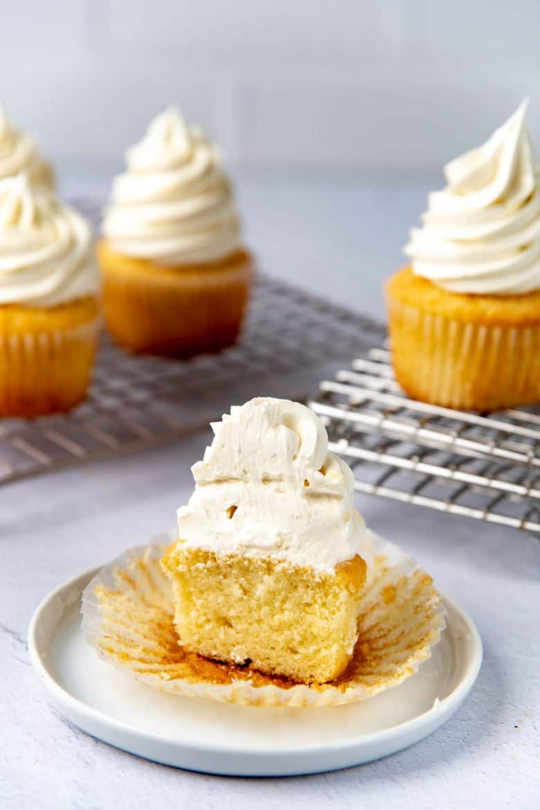 A vanilla cup frosted with easy swiss meringue buttercream cut in half to show frosting texture